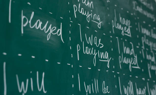 Hand writing on a chalkboard in an language english class. stock photo