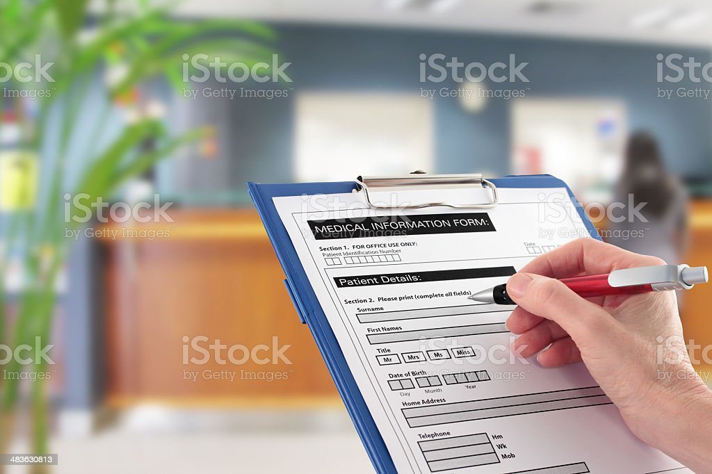 Hand Writing on Medical Details Form in Hospital Reception stock photo