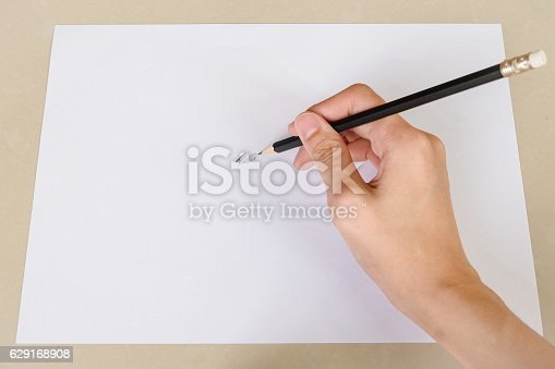 621843818istockphoto Hand writing something by Pencil in white paper 629168908