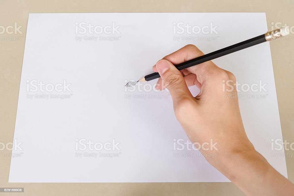 Hand writing something by Pencil in white paper stock photo