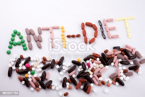 istock Hand writing text caption inspiration Medical care concept written with pills drugs capsule word ANTI DIET On white isolated background with copy space 862507794