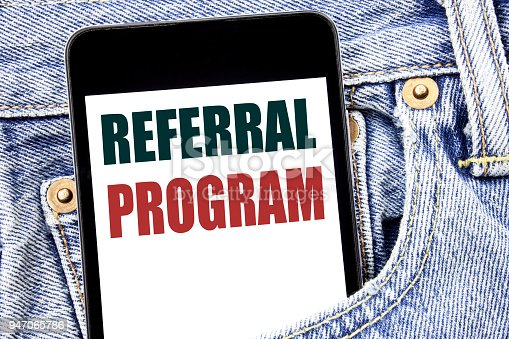 istock Hand writing text caption inspiration showing Referral Program. Business concept for Refer Marketing  written on smartphone in the jeans pants. Blue background. 947065786