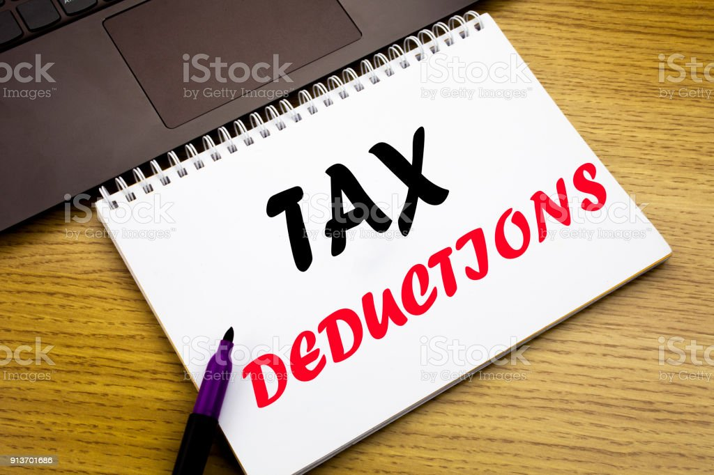 Hand writing text caption inspiration showing Tax Deductions. Business concept for Finance Incoming Tax Money Deduction written on notebook book on the wooden background in the Office with laptop stock photo
