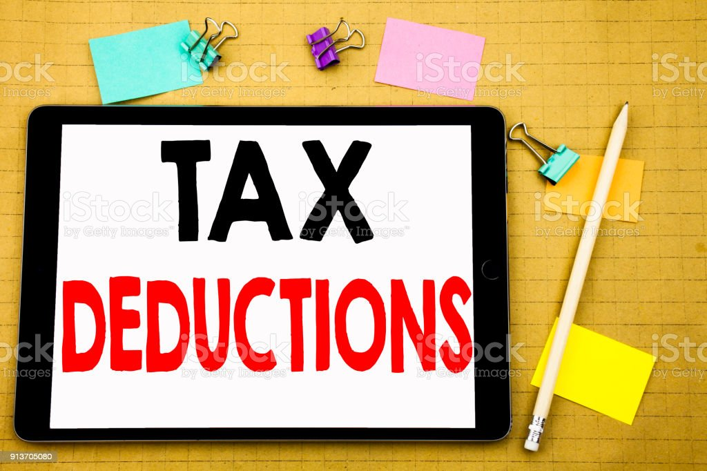 Hand writing text caption inspiration showing Tax Deductions. Business concept for Finance Incoming Tax Money Deduction Written on tablet laptop, wooden background with sticky note and pen stock photo