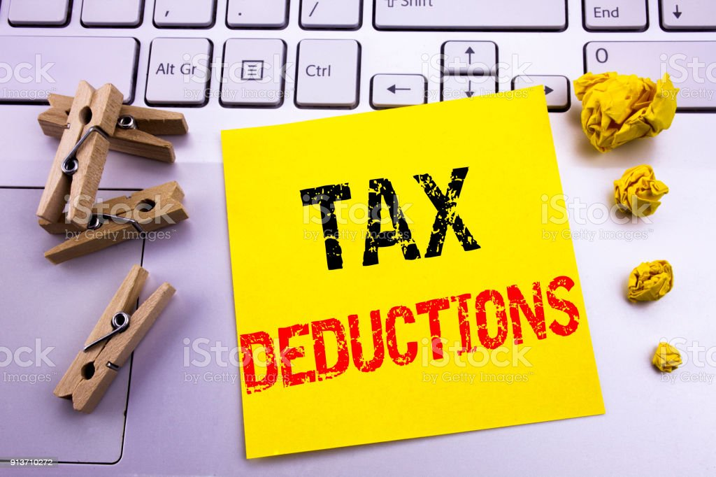 Hand writing text caption inspiration showing Tax Deductions. Business concept for Finance Incoming Tax Money Deduction written on sticky note paper on the white keyboard background. stock photo