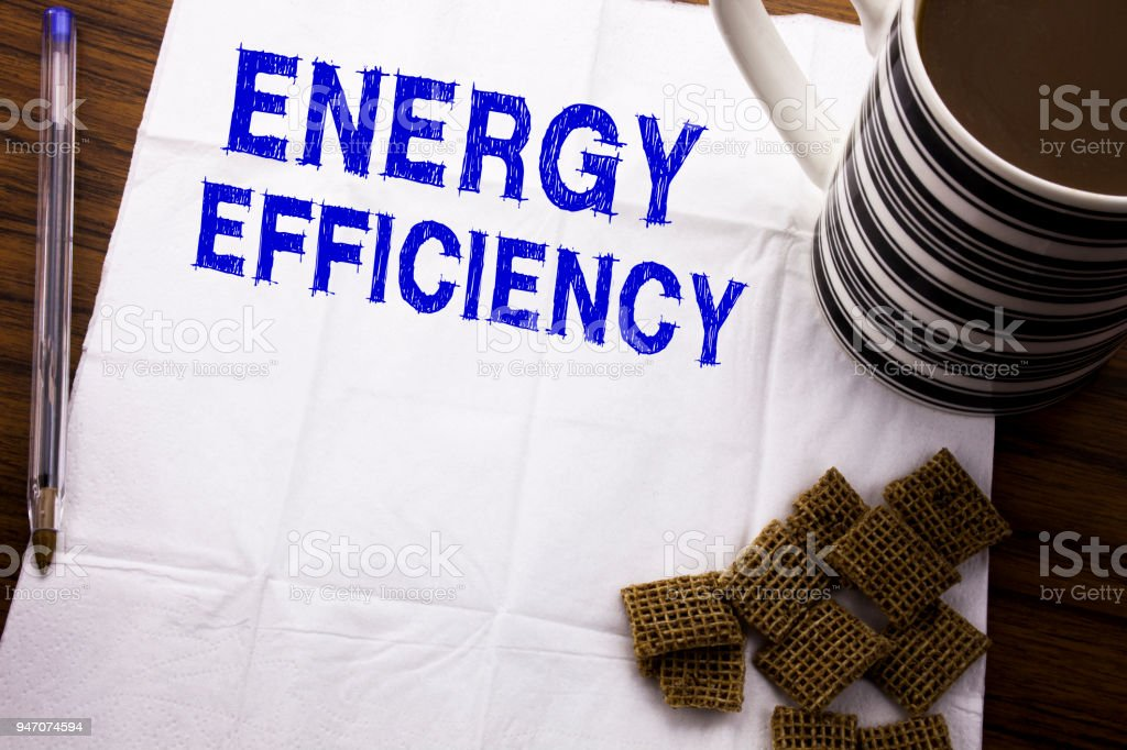 Hand writing text caption showing Energy Efficiency. Business concept for Electricity Ecology written on tissue paper on the wooden background with pen and healthy coffee in the restaurant stock photo