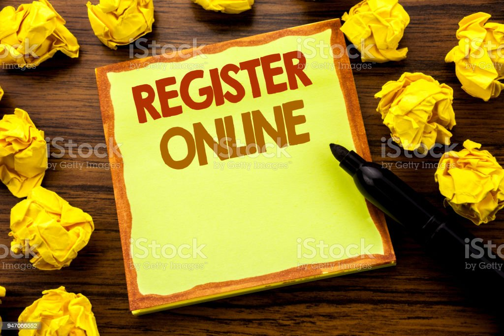 Hand writing text caption showing Register Online. Business concept for Internet Subscribe Written on sticky note paper, wooden background with marker folded yellow paper meaning thinking stock photo