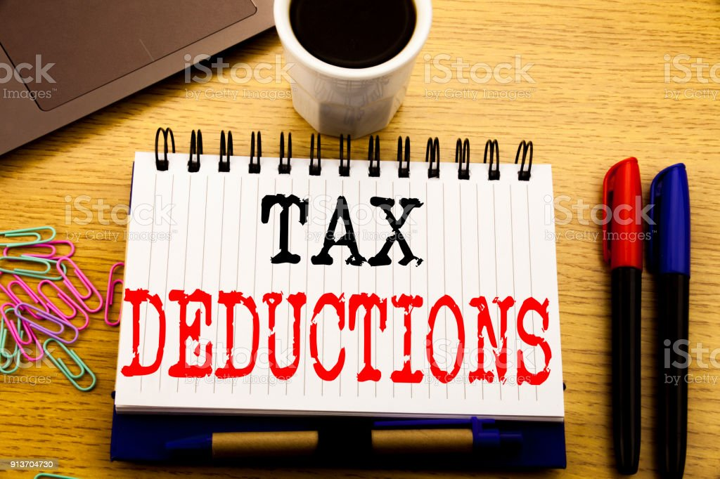 Hand writing text caption showing Tax Deductions. Business concept for Finance Incoming Tax Money Deduction written on notebook book on the wooden background in the Office with laptop coffee stock photo