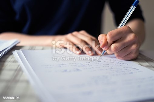 The photo is taken indoors with copy space. A woman is writing words on white paper and doing the homeworks.