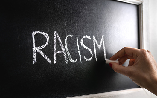 Hand writing the word racism on blackboard. Stop hate. Against prejudice and violence. Lecture about discrimination in school.