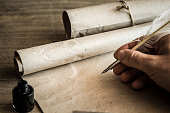 istock Hand writing with old quill pen on the old paper. Historical atmosphere. Empty place for a text. 838545534