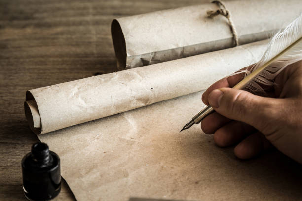 hand writing with old quill pen on the old paper. historical atmosphere. empty place for a text. - scroll stock photos and pictures