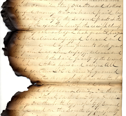 An old letter that's been singed from fire on the edges.