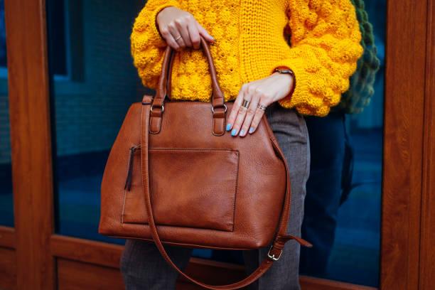 handtas. vrouw het houden van stijlvolle tas en het dragen van gele trui. herfst vrouwelijke kleren en accessoires. mode - handtas stockfoto's en -beelden
