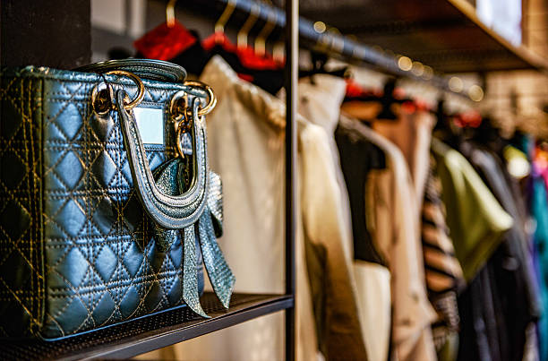 Handbags and clothes in a fashion store Handbags and clothes in a fashion store boutique stock pictures, royalty-free photos & images