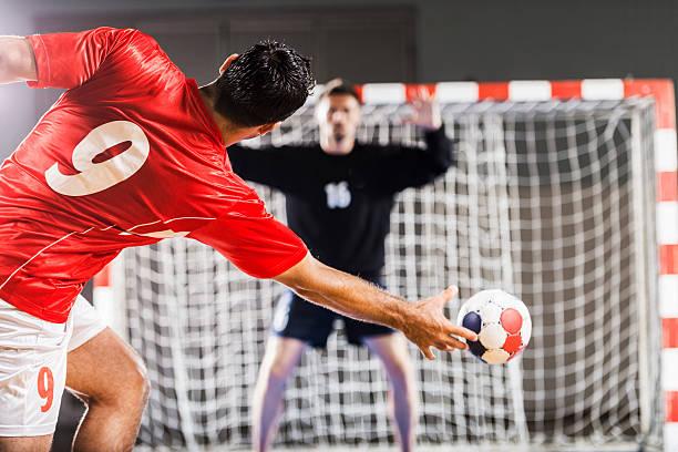 handball player in red shooting toward a net - handboll bildbanksfoton och bilder
