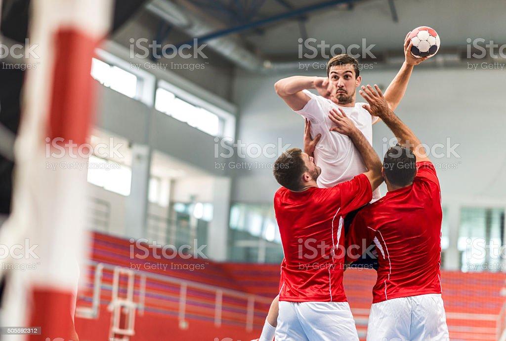 Handball player jumping and shooting at goal. stock photo