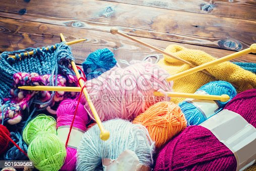 view from above on a wooden table with lots of balls of wool and knitting needles. Place for text