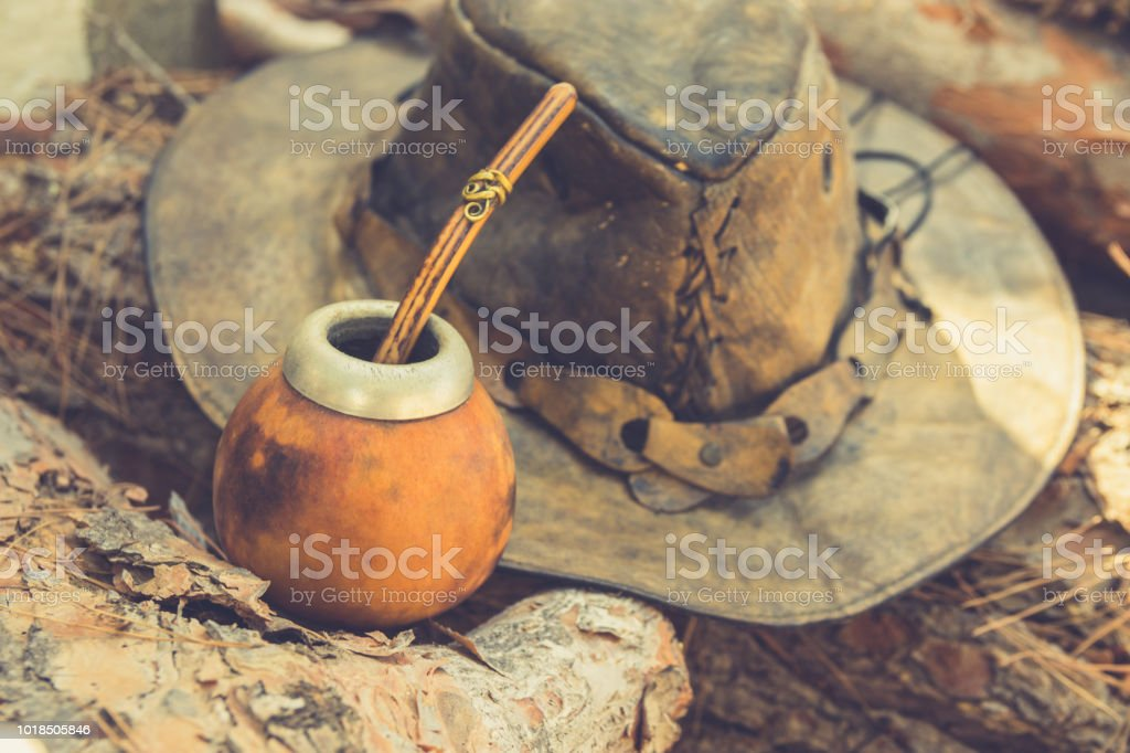 Handcrafted Artisan Yerba Mate Tea Calabash Gourd with Straw Leather Hat on Wood Logs in Forest. Travel Wanderlust Concept. Earthy Tones. Traditional Argentinian Latin American Brewing Cup stock photo