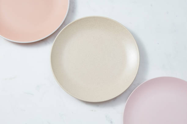 Handcrafted clay empty plates covered with glazed in in pastel colors on a gray concrete background. stock photo