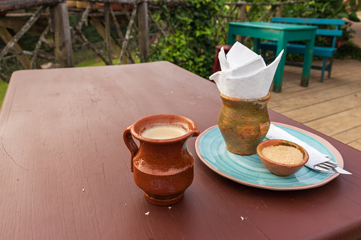 Handcrafted coffee cup with milk on  a wooden table at the mountains of guatemala , travel concept