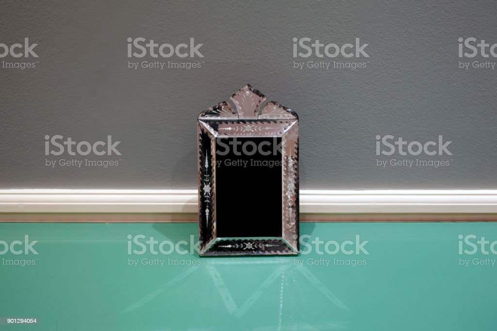 Handcrafted Venetian mirror on a green glass table inside a room stock photo