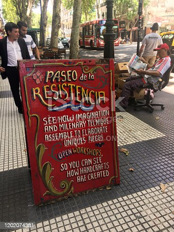 Buenos Aires, Argentina - January 23, 2020: Wooden banner standing on the sidewalk advertising place selling local handcrafts in Avenida de Mayo in the city downtown. This area is crowded with tourists and local craftspersons that want to sell their locally made products