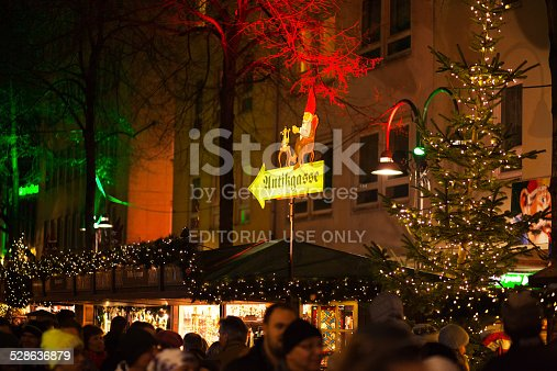 Cologne, Germany - December 14, 2014: Scene on xmas market in Altstadt of Cologne, part of handcraft things. Many people are walking between boothes in aisle. Focus is on sign for this part, socalled Antikgasse, with Heinzelmännchen on top.