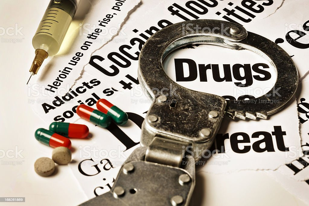 Handcuff frames drugs headline; hypodermic, tablets and capsules rest alongside royalty-free stock photo