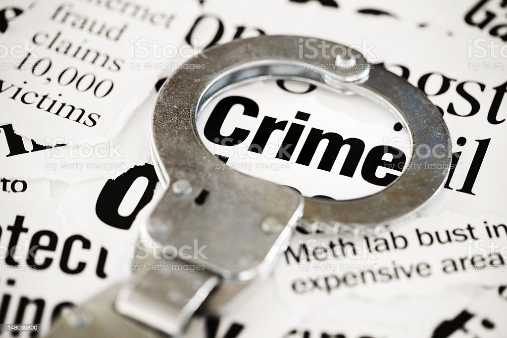 Handcuff rests on crime headline in pile of newspaper cuttings stock photo