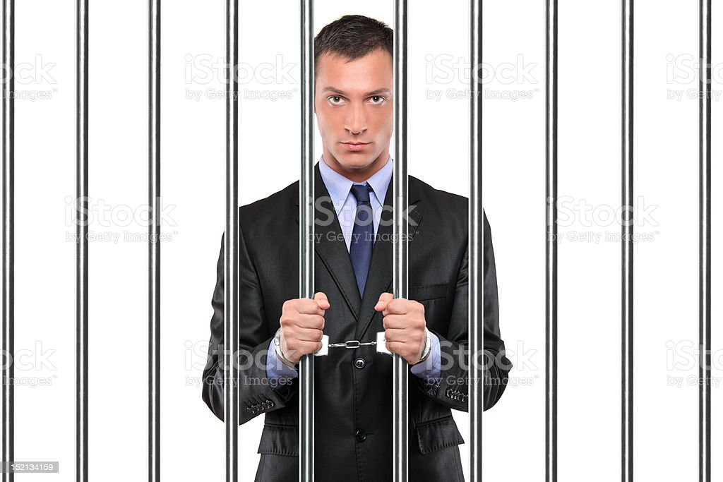 Handcuffed businessman in jail holding bars royalty-free stock photo