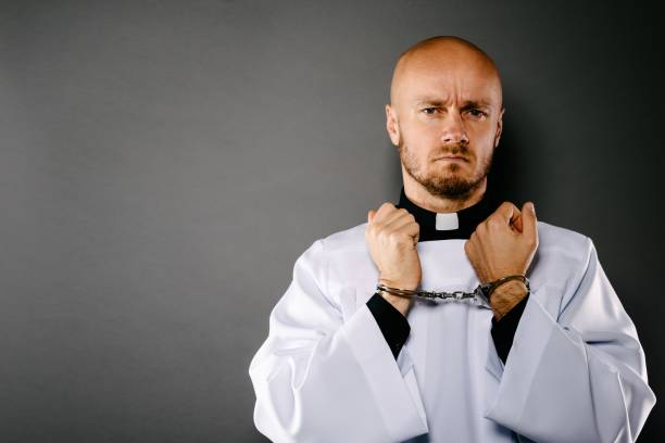 Handcuffed Catholic priest Handcuffed Catholic priest. Church harassment and crime concept clergy stock pictures, royalty-free photos & images