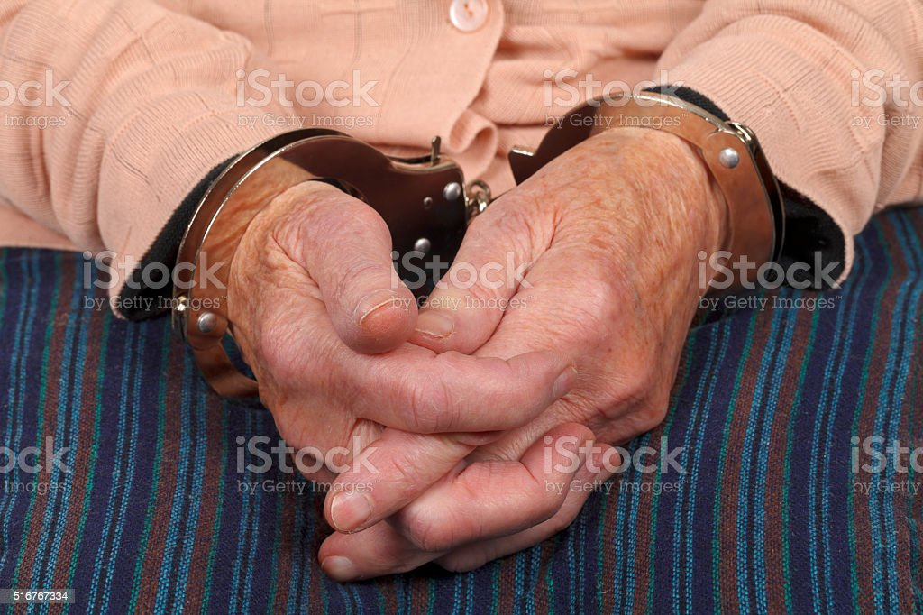 Handcuffed  elderly woman stock photo