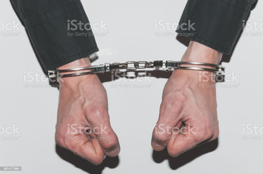 Handcuffed hands of arrested criminal man in handcuffs on police station table. stock photo
