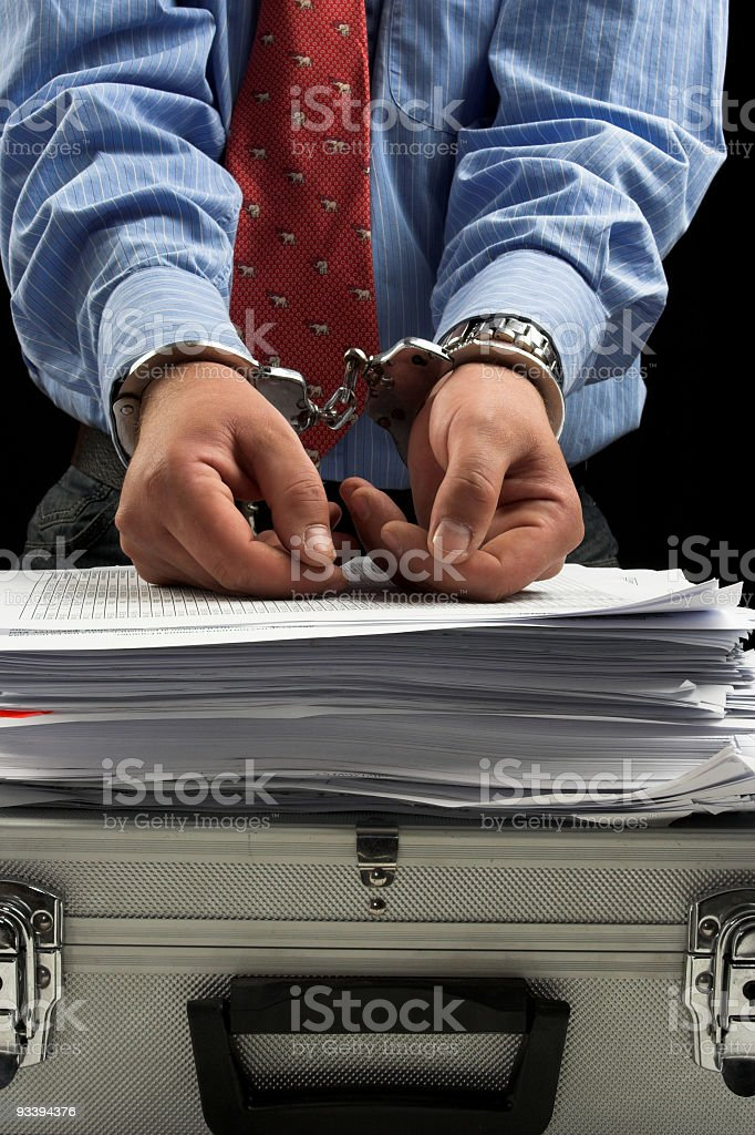 Handcuffed hands on a stack of papers and metal briefcase stock photo