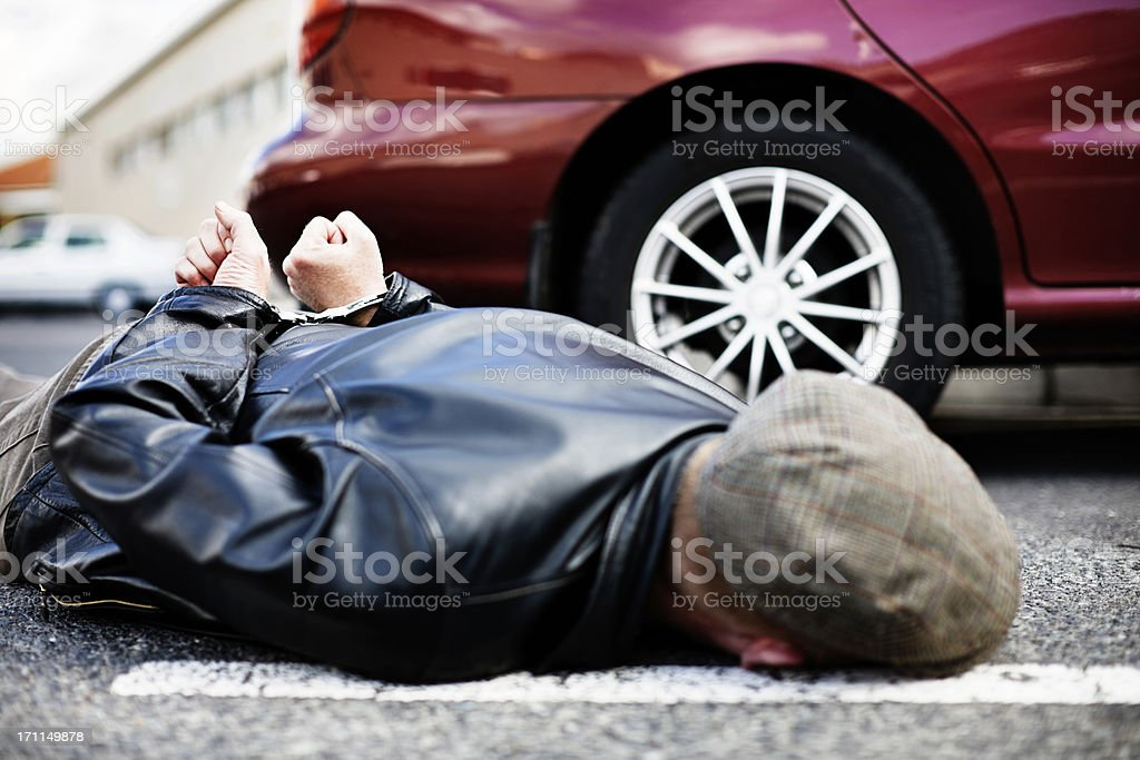 Handcuffed man lies in road next to car stock photo