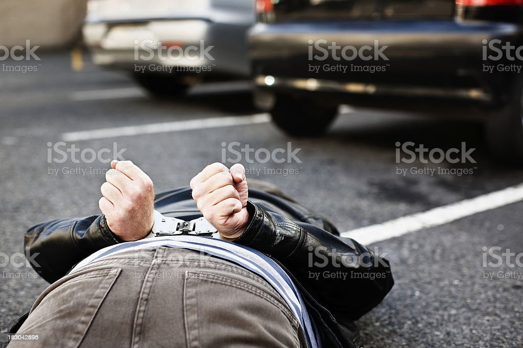 Handcuffed man lies prone next to parked cars royalty-free stock photo