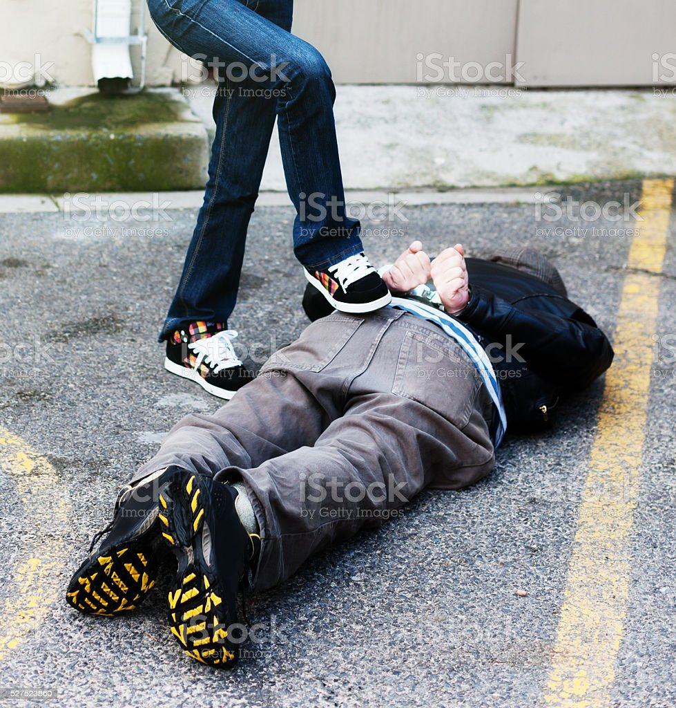 Handcuffed man lying in road, female foot holding him down stock photo