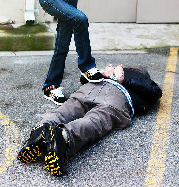 Handcuffed man lying in road, female foot holding him down Unrecognizably cropped woman's leg in jeans places foot on a captured, handcuffed criminal lying in the street. face down stock pictures, royalty-free photos & images