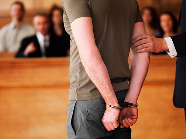 Handcuffed man standing in courtroom stock photo