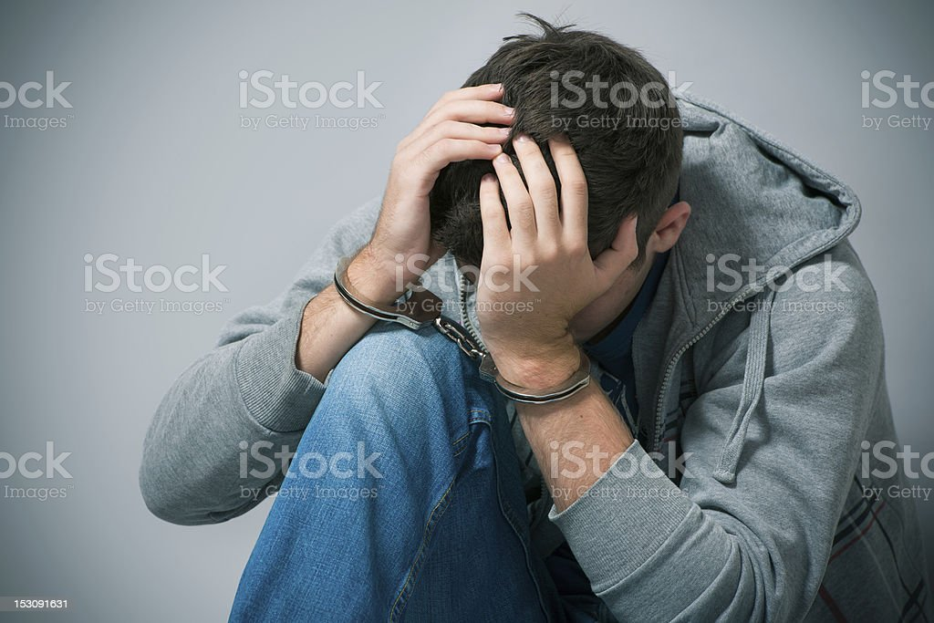 A handcuffed teenager holding his head in shame stock photo