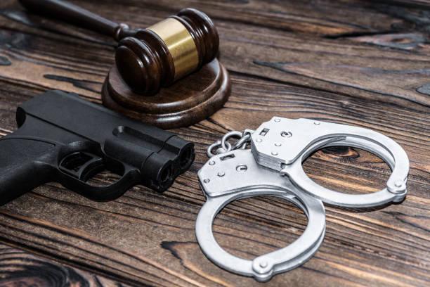 handcuffs, a judge hammer, a gun on a wooden background. criminal offense stock photo