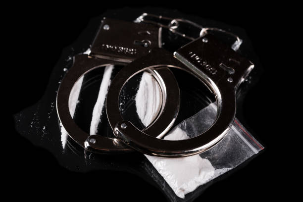 Handcuffs and cocaine stock photo