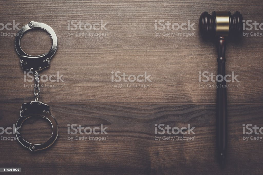handcuffs and judge gavel on wooden background stock photo