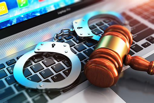 istock Handcuffs and judge mallet on laptop keyboard 910651416