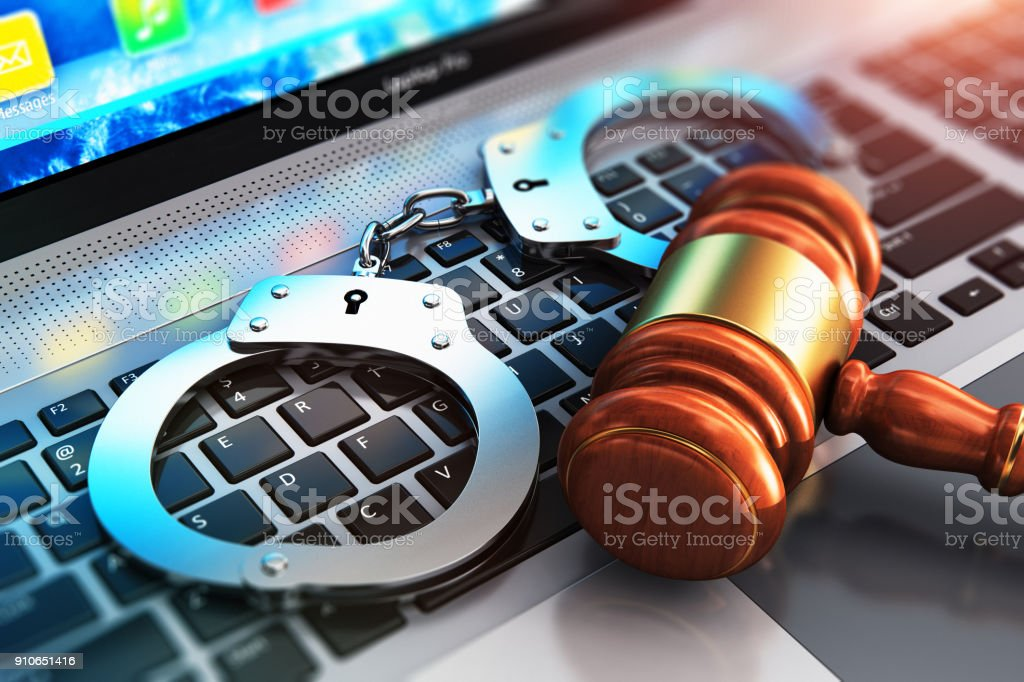 Handcuffs and judge mallet on laptop keyboard stock photo