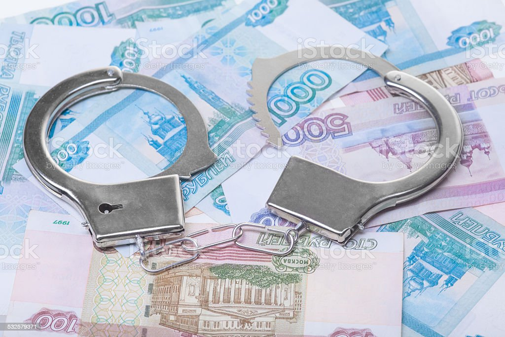 handcuffs and money isolated financial crime. Steel handcuffs and money, closeup 2015 Stock Photo