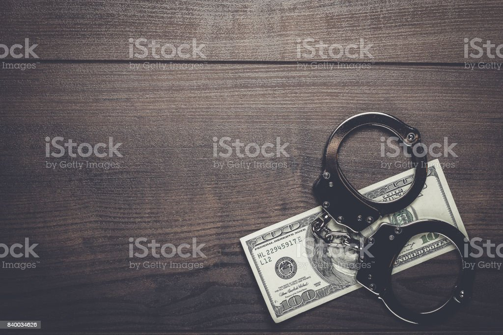 handcuffs and one hundred dollars background stock photo
