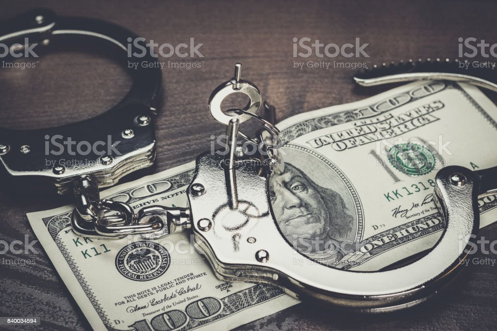 handcuffs and one hundred dollars on the table stock photo