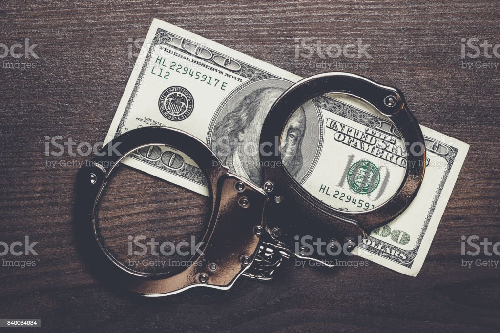 handcuffs and one hundred dollars on wooden table stock photo